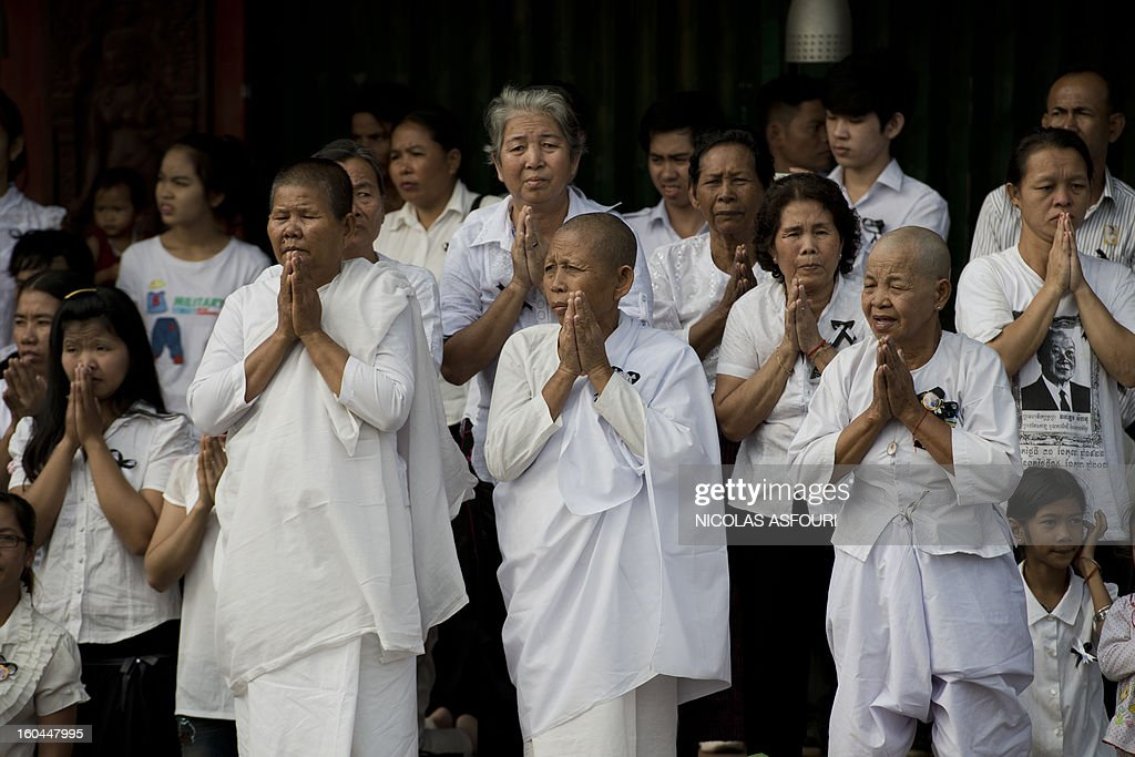 Cambodian people pray as they look at the funeral procession of the late former King Norodom Sihanouk near the the Royal Palace in Phnom Penh on February 1, 2013. Sihanouk, who abdicated in 2004 after steering Cambodia through six decades marked by independence from France, civil war, the murderous Khmer Rouge regime and finally peace, died of a heart attack in Beijing on October 15, 2012 and will be cremated on February 4. AFP PHOTO / Nicolas ASFOURI
