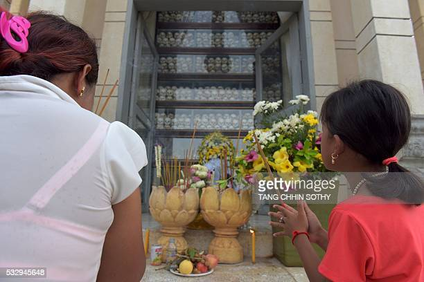 Cambodian people pray during the annual 'Day of Anger' at the Choeung Ek killing fields memorial in Phnom Penh on May 20 2016 More than 1000 people...
