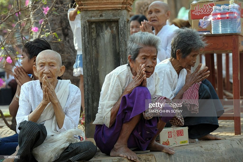 Cambodian people pray during the Meak Bochea Buddhist celebration at the Oddong mountain in Kandal province, some 40 kilometers north of Phnom Penh on February 25, 2013. Thousands of Cambodian followers gathered at the temple for offerings to hundreds of Buddhish monks to mark Meak Bochea day, which marks when Buddha declared he would die in three months.