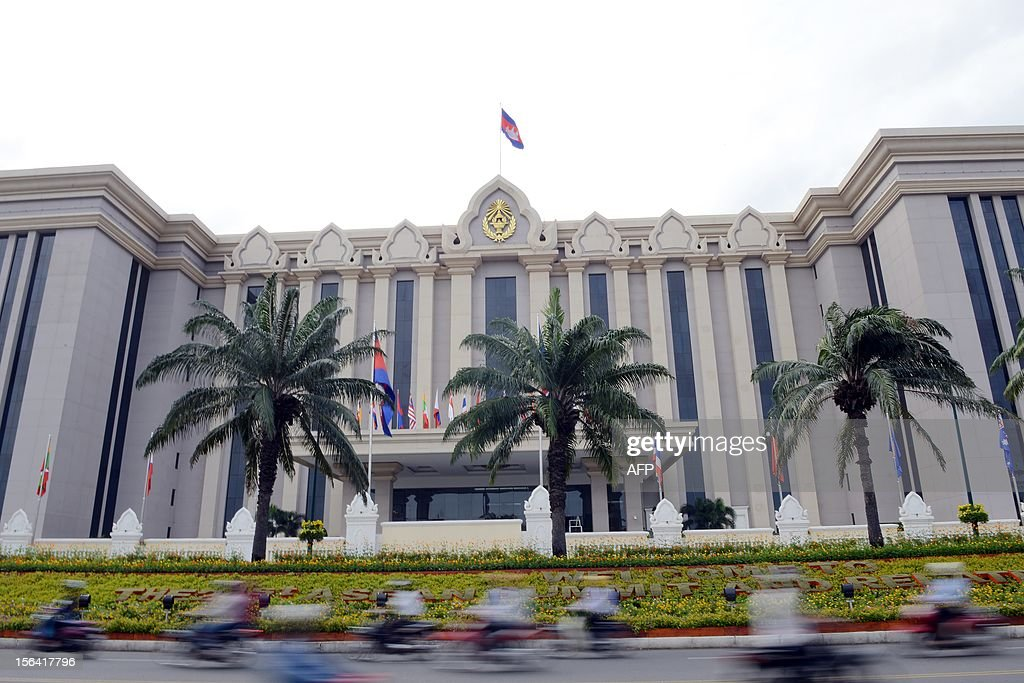Cambodian people ride their motorbikes past the Peace Palace build the place for the 21st Association of Southeast Asian Nations summit and Related...