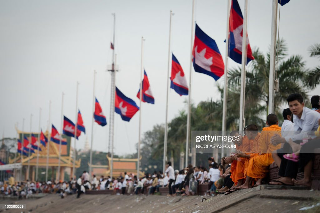Cambodian people sit on the river bank with the national flag at half mast as people come to pray and pay their respect for the late former king Norodom Sihanouk near the Royal Palace in Phnom Penh on February 3, 2013. Thousands of Cambodians have paid their last respects to their beloved former king Norodom Sihanouk as his body lay in state ahead of his cremation on February 4. AFP PHOTO/ Nicolas ASFOURI