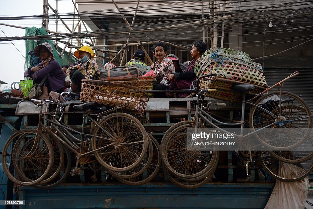 Cambodian people sit on the roof of a truck as it travels along a street in Phnom Penh on January 3, 2013. Written off as a failed state after the devastating 1975-1979 Khmer Rouge regime and several decades of civil war, Cambodia has used garment and footwear exports and tourism to help improve its economy, but remains one of the world's poorest countries with around 30 percent of its 14 million people living on less than a dollar a day.