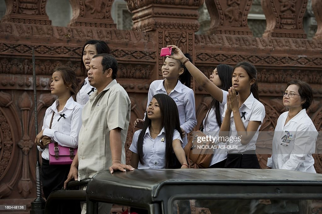 Cambodian people stand on the back of a pick up truck to try to watch the funeral procession of the late former King Norodom Sihanouk near the the Royal Palace in Phnom Penh on February 1, 2013. Sihanouk, who abdicated in 2004 after steering Cambodia through six decades marked by independence from France, civil war, the murderous Khmer Rouge regime and finally peace, died of a heart attack in Beijing on October 15, 2012 and will be cremated on February 4. AFP PHOTO / Nicolas ASFOURI