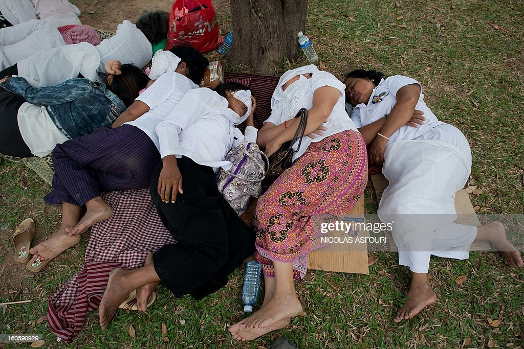 Cambodian people take a nap before going to pray and pay their respects for the late former king Norodom Sihanouk near the Royal Palace in Phnom Penh on February 3, 2013. Thousands of Cambodians have paid their last respects to their beloved former king Norodom Sihanouk as his body lay in state ahead of his cremation on February 4. AFP PHOTO/ Nicolas ASFOURI