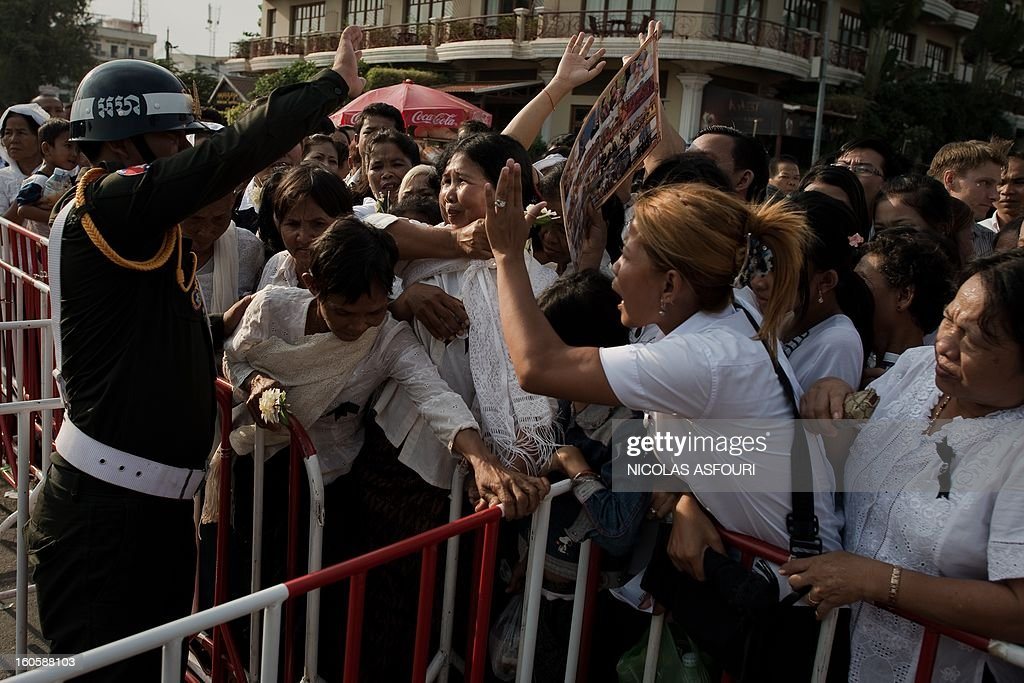 Cambodian people try to make their way through gates secured by police officers as they come to pray and pay their respect for the late former king Norodom Sihanouk near the Royal Palace in Phnom Penh on February 3, 2013. Thousands of Cambodians have paid their last respects to their beloved former king Norodom Sihanouk as his body lay in state ahead of his cremation on February 4. AFP PHOTO/ Nicolas ASFOURI