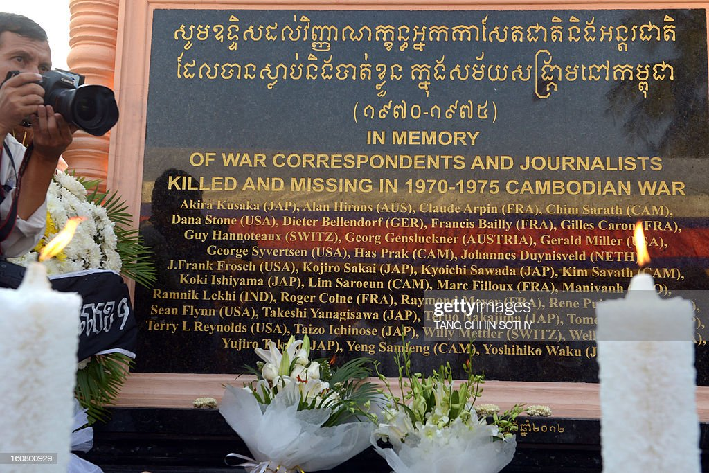 A Cambodian photographer (L) takes picture next to a memorial sign at a park in front of the Le Royal hotel on February 6, 2013. Cambodia on February 6 officially unveiled a memorial to dozens of foreign and local journalists killed covering the country's 1970-75 war won by the communist Khmer Rouge regime. Led by 'Brother Number One' Pol Pot, who died in 1998, the Khmer Rouge wiped out nearly a quarter of the population through starvation, overwork or execution during its 1975-1979 rule in a bid to forge a communist utopia.