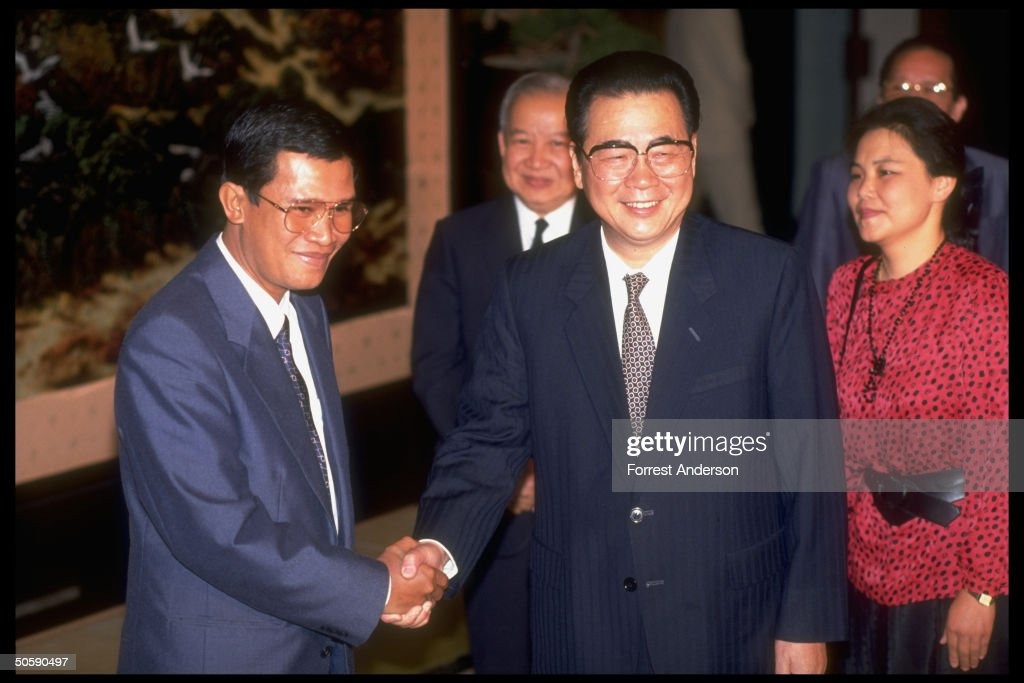 Cambodian PM Hun Sen (L) shaking hands w. PM Li Peng, hosting mtg. of Cambodian Supreme Natl. Council, w. Prince Sihanouk (C), in tow.