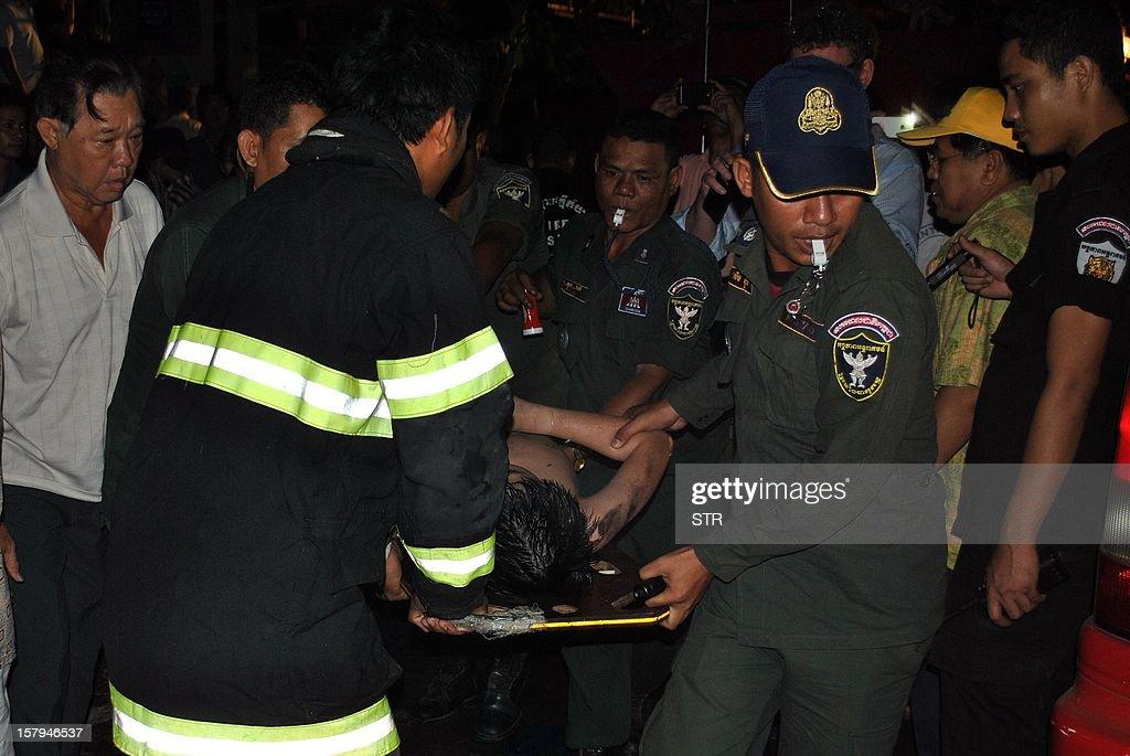 Cambodian police officers use a stretcher to carry a victim (C) from a fire in a night market in Siem Reap province, some 300 kilometers northwest of Phnom Penh on December 08, 2012. Eight people, including four children, were killed in a fire that tore through a popular night market in the Cambodian tourist town of Siem Reap early December 8, police said.