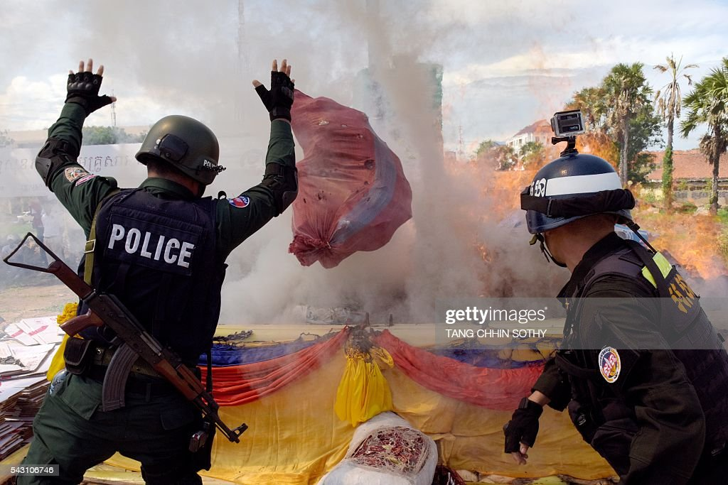 Cambodian police officials throw drugs as they burn during a destruction ceremony to mark the UN's 'International Day against Drug Abuse and Illicit Trafficking' in Phnom Penh on June 26, 2016. Cambodian authorities burned nearly 2 tons of seized drugs during the event. / AFP / TANG