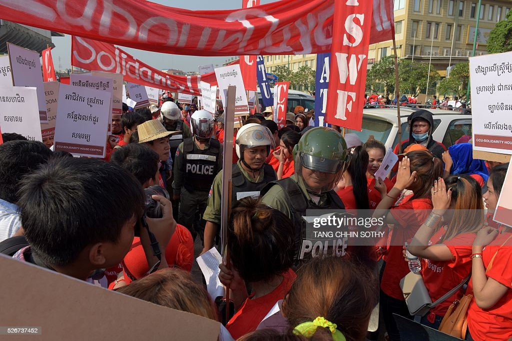 Cambodian police officials walk past workers gathering to mark May Day, or International Workers Day, in Phnom Penh on May 1, 2016. Activists around the world mark May Day with marches demanding better working conditions, more jobs and higher wages. / AFP / TANG