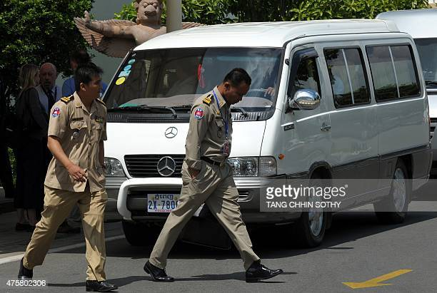 Cambodian police walk past a van transporting refugees held under Australian custody in the Central Pacific island of Nauru following their arrival...