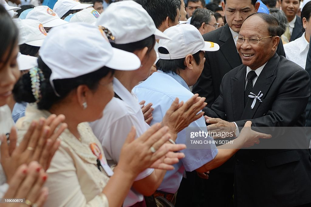 Cambodian president of the National Assembly and vice president of Cambodian People's Party (CPP) Heng Samrin (R) greets supporters during a CPP ceremony marking the 34th anniversary of the fall of the Khmer Rouge regime at the CPP headquarters in Phnom Penh on January 7, 2013. Some Cambodians criticise the January 7 anniversary, saying it represents the start of a decade-long occupation by Vietnam rather than a day of liberation while Hun Sen, a former Khmer Rouge cadre before he fled to Vietnam in 1977 and joined the resistance, has been Cambodia's prime minister since 1985.