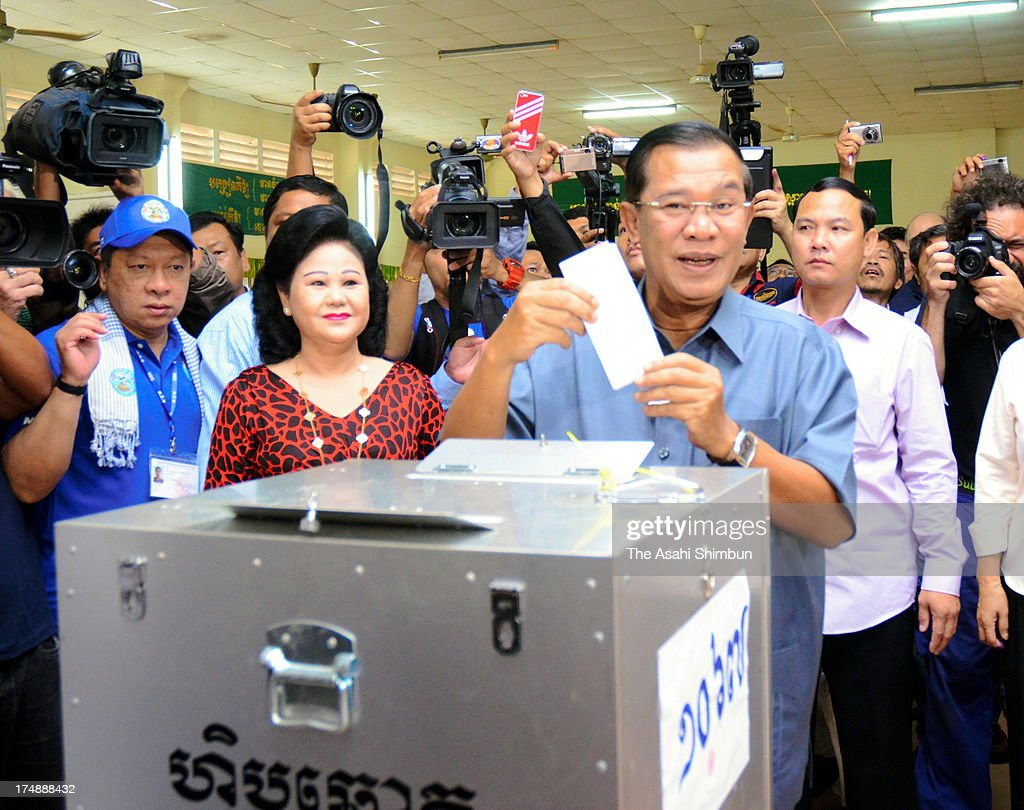 Cambodian Prime Minister <a gi-track='captionPersonalityLinkClicked' href=/galleries/search?phrase=Hun+Sen&family=editorial&specificpeople=224084 ng-click='$event.stopPropagation()'>Hun Sen</a> (C) casts his vote with his wife Bun Rany (L) during the Cambodian general elections on July 28, 2013 in Phnom Penh, Cambodia. Cambodians go to the polls today in the fifth parliamentary election since 1993. 123 seats in the National Assembly are up for grabs to eight listed parties, with the main contenders being the ruling Cambodian Peoples Party (CPP) and the leading opposition Cambodia National Rescue Party (CNRP) led by Sam Rainsy.