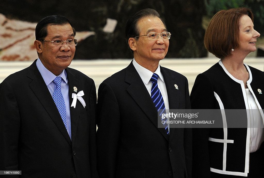 Cambodian Prime Minister Hun Sen, Chinese Prime Minister Wen Jiabao and Australian Prime Minister <a gi-track='captionPersonalityLinkClicked' href=/galleries/search?phrase=Julia+Gillard&family=editorial&specificpeople=787281 ng-click='$event.stopPropagation()'>Julia Gillard</a> stand for a family picture ahead of the 7th East Asia Summit in Phnom Penh on November 20, 2012. The Association of Southeast Asian Nations (ASEAN) nations were set to officially launch negotiations to create an enormous free trade pact with China, Japan, India, South Korea, Australia and New Zealand. AFP PHOTO/Christophe ARCHAMBAULT