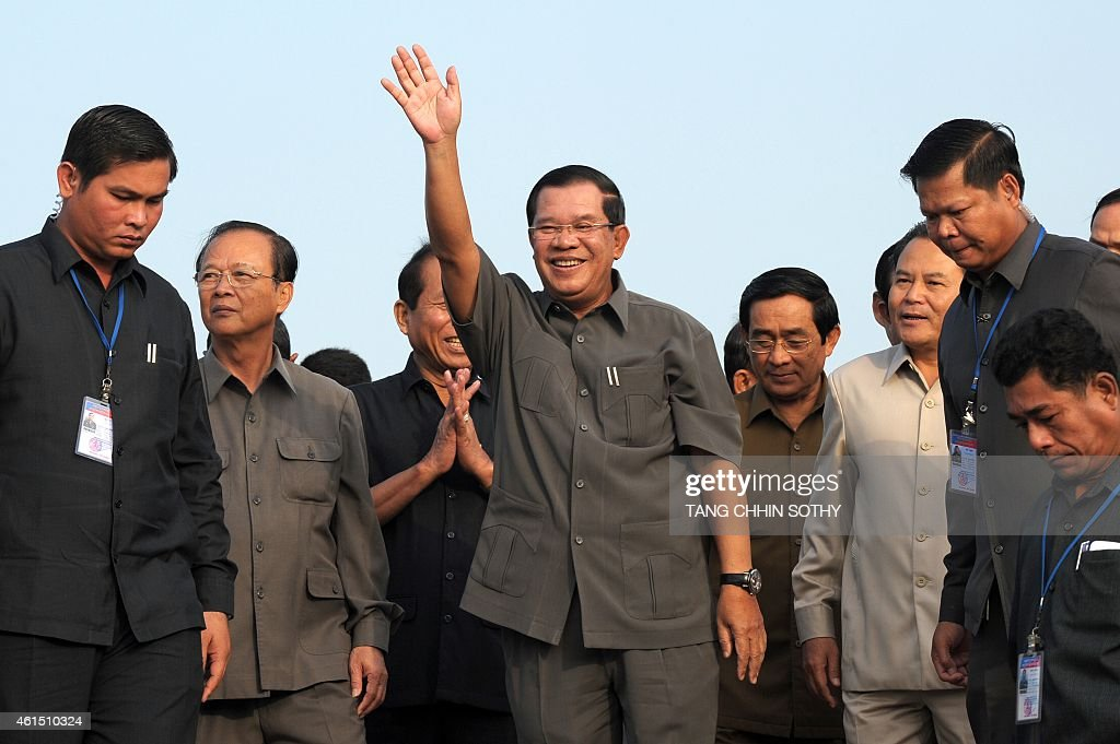 Cambodian Prime Minister <a gi-track='captionPersonalityLinkClicked' href=/galleries/search?phrase=Hun+Sen&family=editorial&specificpeople=224084 ng-click='$event.stopPropagation()'>Hun Sen</a> (C) greets people during a ceremony for casting concrete to connect Neak Loeung bridge in Kandal province on January 14, 2014. Cambodian strongman <a gi-track='captionPersonalityLinkClicked' href=/galleries/search?phrase=Hun+Sen&family=editorial&specificpeople=224084 ng-click='$event.stopPropagation()'>Hun Sen</a> marked three decades as premier on January 14, hailing his role in rebuilding the war-torn nation, as rights groups lambasted him for using 'violence, repression and corruption' to cling onto power. AFP PHOTO / TANG CHHIN SOTHY