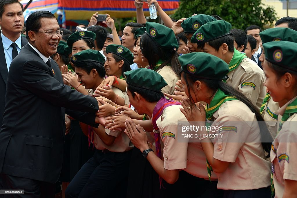 Cambodian Prime Minister Hun Sen (L) greets scouts during a Cambodian People's Party (CPP) ceremony marking the 34th anniversary of the fall of the Khmer Rouge regime at the CPP headquarters in Phnom Penh on January 7, 2013. Some Cambodians criticise the January 7 anniversary, saying it represents the start of a decade-long occupation by Vietnam rather than a day of liberation while Hun Sen, a former Khmer Rouge cadre before he fled to Vietnam in 1977 and joined the resistance, has been Cambodia's prime minister since 1985. AFP PHOTO/ TANG CHHIN SOTHY