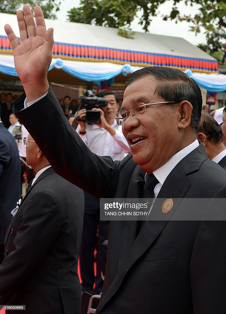 Cambodian Prime Minister Hun Sen (R) greets supporters during a Cambodian People's Party (CPP) ceremony marking the 34th anniversary of the fall of the Khmer Rouge regime at the CPP headquarters in Phnom Penh on January 7, 2013. Some Cambodians criticise the January 7 anniversary, saying it represents the start of a decade-long occupation by Vietnam rather than a day of liberation while Hun Sen, a former Khmer Rouge cadre before he fled to Vietnam in 1977 and joined the resistance, has been Cambodia's prime minister since 1985.
