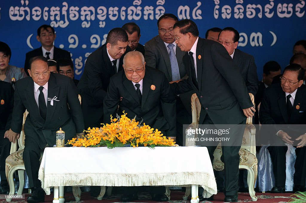 Cambodian Prime Minister Hun Sen (2nd R) helps Cambodia's president of the senate and president of the Cambodian People's Party (CPP) Chea Sim (C) to stand up as president of the National Assembly and vice president of Cambodian People's Party (CPP) Heng Samrin (L) rises from his chair during a CPP ceremony marking the 34th anniversary of the fall of the Khmer Rouge regime at CPP headquarters in Phnom Penh on January 7, 2013. Some Cambodians criticise the January 7 anniversary, saying it represents the start of a decade-long occupation by Vietnam rather than a day of liberation while Hun Sen, a former Khmer Rouge cadre before he fled to Vietnam in 1977 and joined the resistance, has been Cambodia's prime minister since 1985. AFP PHOTO/ TANG CHHIN SOTHY