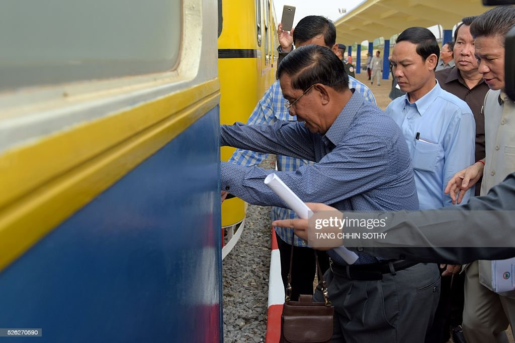 Cambodian Prime minister Hun Sen (C) is photographed outside a train compartment at the Phnom Penh train station on April 30, 2016, as the railway service resumes after years of suspension. Cambodia's sole passenger train resumed a regular weekend service April 30 after years of suspension, with Prime Minister Hun Sen climbing aboard to inaugurate the first trip. The Southeast Asian country has more than 600 kilometres of railroad extending from its northern border with Thailand down to the southern coast, but decades of war and neglect have left vast stretches of track damaged. / AFP / TANG