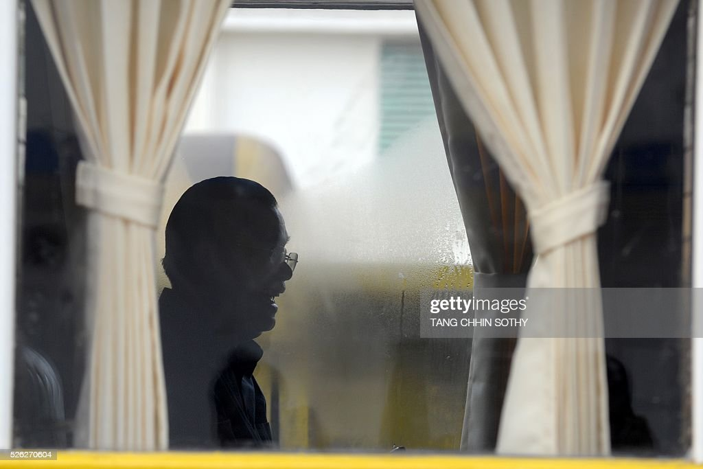 Cambodian Prime minister Hun Sen (C) is seen from a train compartment window at the Phnom Penh train station on April 30, 2016, as the railway service resumes after years of suspension. Cambodia's sole passenger train resumed a regular weekend service April 30 after years of suspension, with Prime Minister Hun Sen climbing aboard to inaugurate the first trip. The Southeast Asian country has more than 600 kilometres of railroad extending from its northern border with Thailand down to the southern coast, but decades of war and neglect have left vast stretches of track damaged. / AFP / TANG