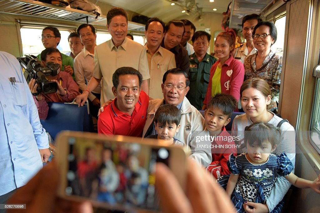 Cambodian Prime minister Hun Sen (C) poses with passengers on a train at the Phnom Penh train station on April 30, 2016, as the railway service resumes after years of suspension. Cambodia's sole passenger train resumed a regular weekend service April 30 after years of suspension, with Prime Minister Hun Sen climbing aboard to inaugurate the first trip. The Southeast Asian country has more than 600 kilometres of railroad extending from its northern border with Thailand down to the southern coast, but decades of war and neglect have left vast stretches of track damaged. / AFP / TANG