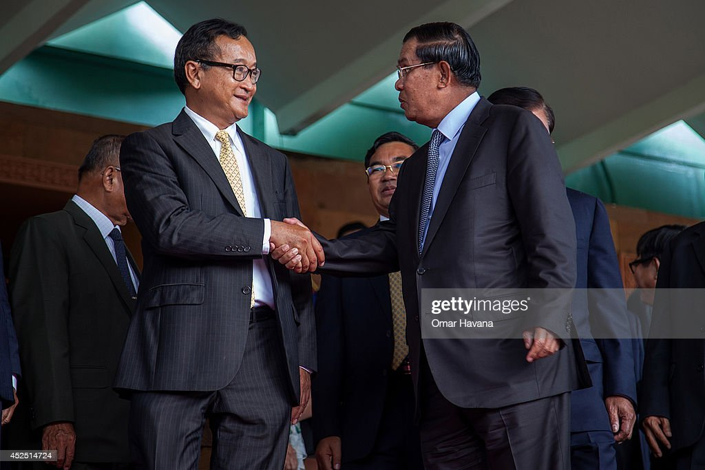 Cambodian Prime Minister Hun Sen shakes hands with the President of the opposition Cambodia National Rescue Party, Sam Rainsy after a meeting during which both parties agree to end the political deadlock on July 22, 2014 in Phnom Penh, Cambodia. Cambodian Prime Minister Hun Sen met today with the President of the opposition Cambodia National Rescue Party, Sam Rainsy, for 'final talks' on an agreement to end the year-long political deadlock between the ruling Cambodian People's Party and the CNRP, a week after eight CNRP Members of Parliament-elect were arrested and charged with crimes of insurrection and incitement to violence. The deal on the table is based on a principle agreement dating back to April 2014 between Hun Sen and Sam Rainsy, which includes a February 2018 national election and reform of the National Election Committee.