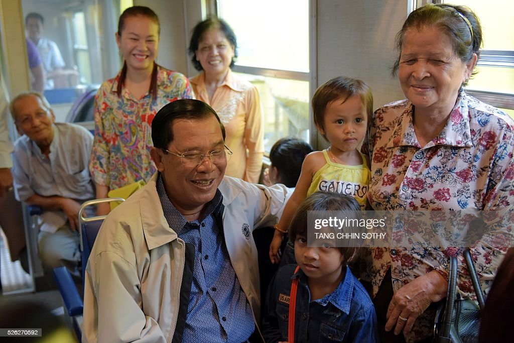 Cambodian Prime minister Hun Sen (C) sits with passengers on a train at the Phnom Penh train station on April 30, 2016, as the railway service resumes after years of suspension. Cambodia's sole passenger train resumed a regular weekend service April 30 after years of suspension, with Prime Minister Hun Sen climbing aboard to inaugurate the first trip. The Southeast Asian country has more than 600 kilometres of railroad extending from its northern border with Thailand down to the southern coast, but decades of war and neglect have left vast stretches of track damaged. / AFP / TANG