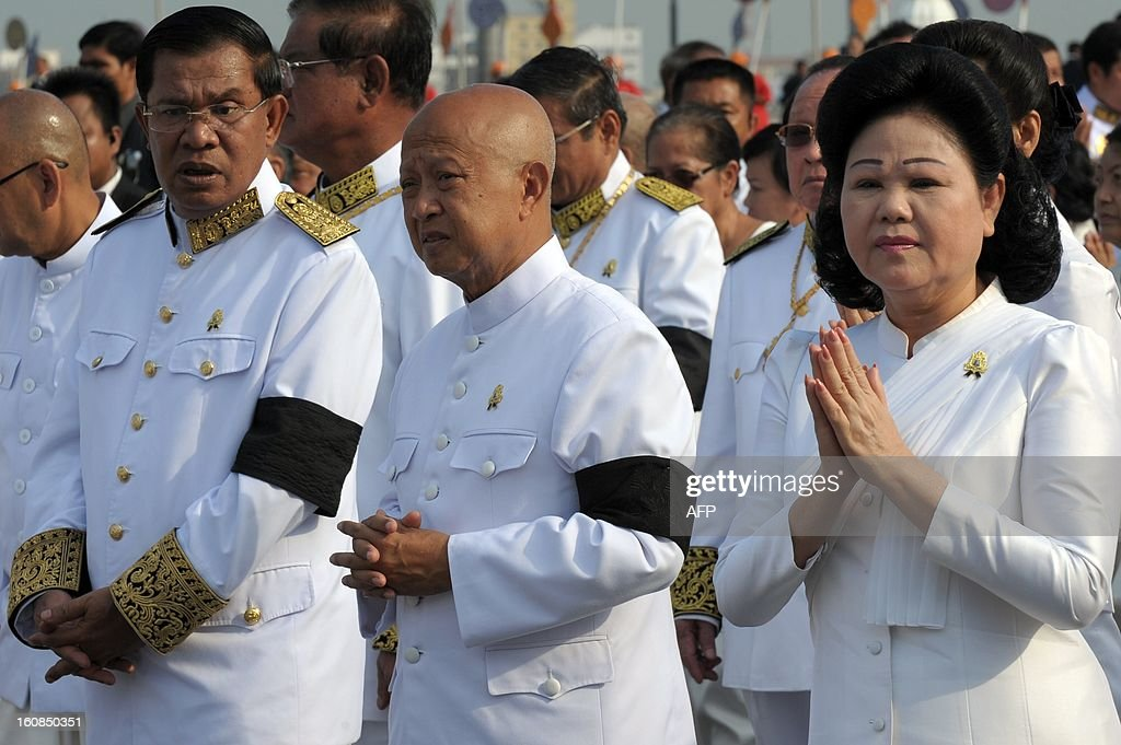 Cambodian Prime Minister Hun Sen (L) talks to Cambodian Prince Norodom Ranariddh (C) as President of the Cambodia Red Cross and Cambodian prime minister 's wife Bunrany (R) prays during the funeral of the late former King Norodom Sihanouk in front of the Royal Palace in Phnom Penh on February 7, 2013 following his cremation on February 4. Cambodia ended the week-long lavish funeral of its revered former King Norodom Sihanouk on February 7, by bringing his bones back to the royal palace.