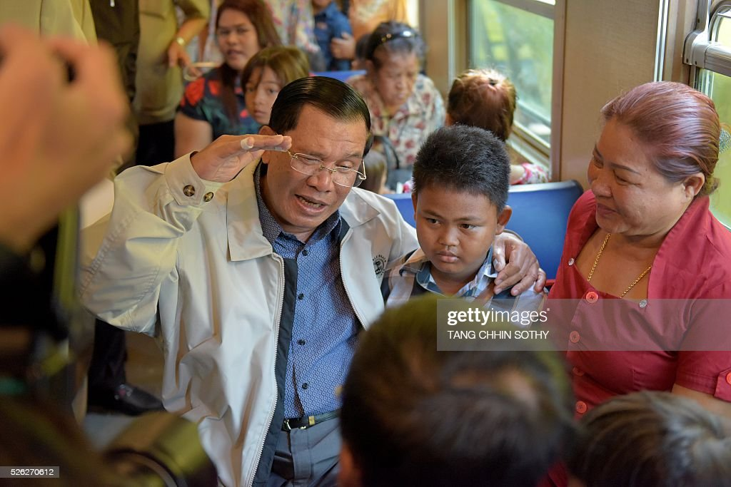 Cambodian Prime minister Hun Sen (L) talks with passengers on a train at the Phnom Penh train station on April 30, 2016, as the railway service resumes after years of suspension. Cambodia's sole passenger train resumed a regular weekend service April 30 after years of suspension, with Prime Minister Hun Sen climbing aboard to inaugurate the first trip. The Southeast Asian country has more than 600 kilometres of railroad extending from its northern border with Thailand down to the southern coast, but decades of war and neglect have left vast stretches of track damaged. / AFP / TANG