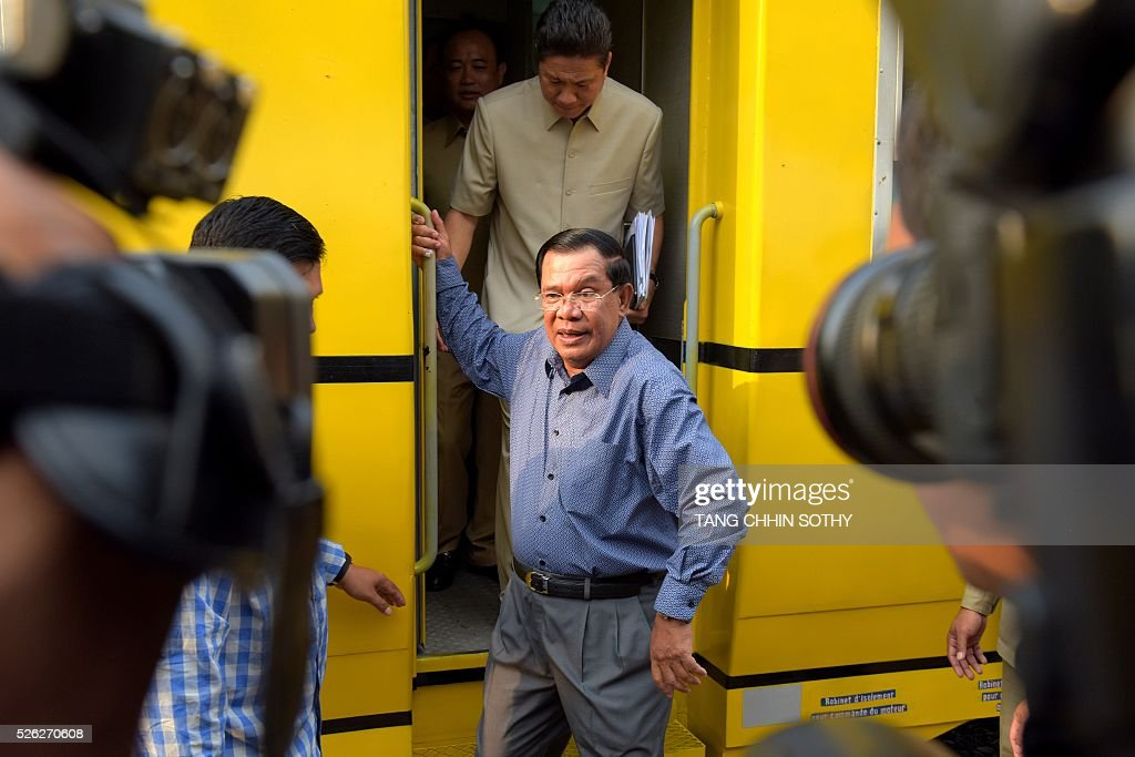 Cambodian Prime minister Hun Sen (C) walks down from a compartment of a train at the Phnom Penh train station on April 30, 2016, as the railway service resumes after years of suspension. Cambodia's sole passenger train resumed a regular weekend service April 30 after years of suspension, with Prime Minister Hun Sen climbing aboard to inaugurate the first trip. The Southeast Asian country has more than 600 kilometres of railroad extending from its northern border with Thailand down to the southern coast, but decades of war and neglect have left vast stretches of track damaged. / AFP / TANG