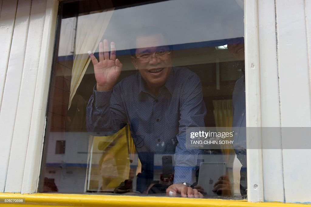 Cambodian Prime minister Hun Sen waves from a train compartment window at the Phnom Penh train station on April 30, 2016, as the railway service resumes after years of suspension. Cambodia's sole passenger train resumed a regular weekend service April 30 after years of suspension, with Prime Minister Hun Sen climbing aboard to inaugurate the first trip. The Southeast Asian country has more than 600 kilometres of railroad extending from its northern border with Thailand down to the southern coast, but decades of war and neglect have left vast stretches of track damaged. / AFP / TANG