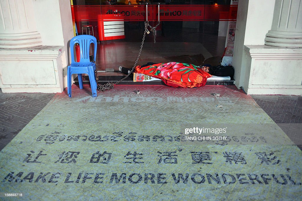 A Cambodian private security guard sleeps in front of a main entrace door of a shop in Phnom Penh on January 3, 2013. Written off as a failed state after the devastating 1975-1979 Khmer Rouge regime and several decades of civil war, Cambodia has used garment and footwear exports and tourism to help improve its economy, but remains one of the world's poorest countries with around 30 percent of its 14 million people living on less than a dollar a day.
