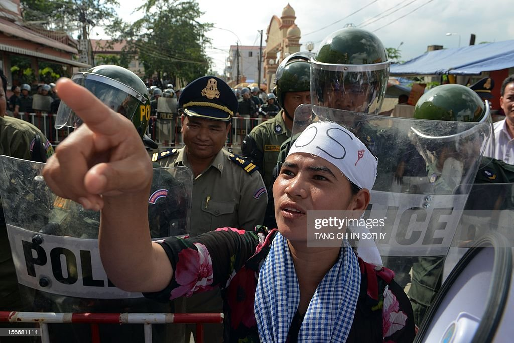 A Cambodian protesters gestures as anti-riot policemen block a road during a protest in Phnom Penh on November 19, 2012 as the Association of Southeast Asian Nations (ASEAN) summit begins meetings. The protesters threatened with eviction at a lake where their committee is based staged a rally with 'SOS' banners urging US President Barack Obama to press the government on land rights during his upcoming visit. Obama on November 19 become the first sitting US president to visit Cambodia for the high-profile East Asia Summit on the sidelines of the Association of Southeast Asian Nations (ASEAN) summit.
