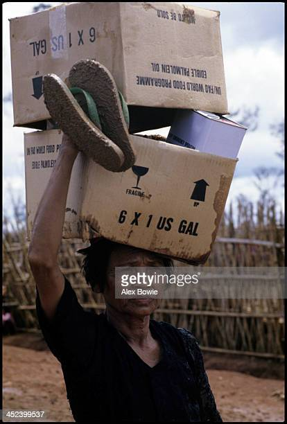A Cambodian refugee carries cooking oil and food supplies donated by the Food and Agriculture Organization of the United Nations World Food Programme...