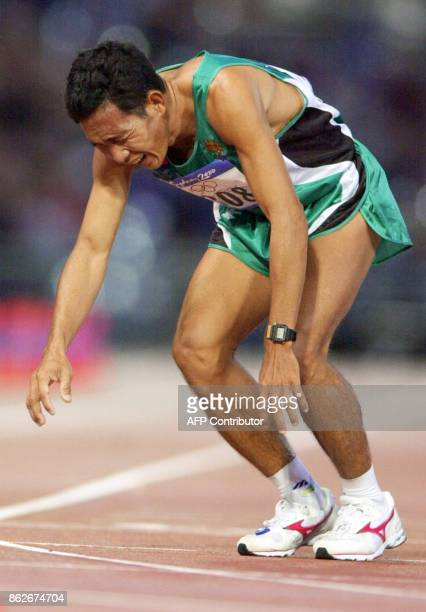 Cambodian Rithya To breaks down exhausted after crossing the finish line next to last of the men's marathon on 01 October 2000 inside the Olympic...