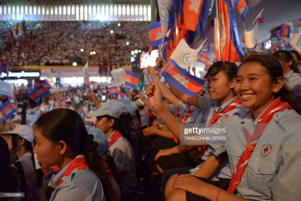 Cambodian scouts wave their national flags and UNESCO flags during an event to mark the fifth anniversary of Preah Vihear temple's world heritage listing, at the National Stadium in Phnom Penh on July 7, 2013. Cambodia on July 7 happily and noisily marked the 5th anniversary of the UNESCO listing of the ancient 11th-century Preah Vihear temple as a World Heritage site.