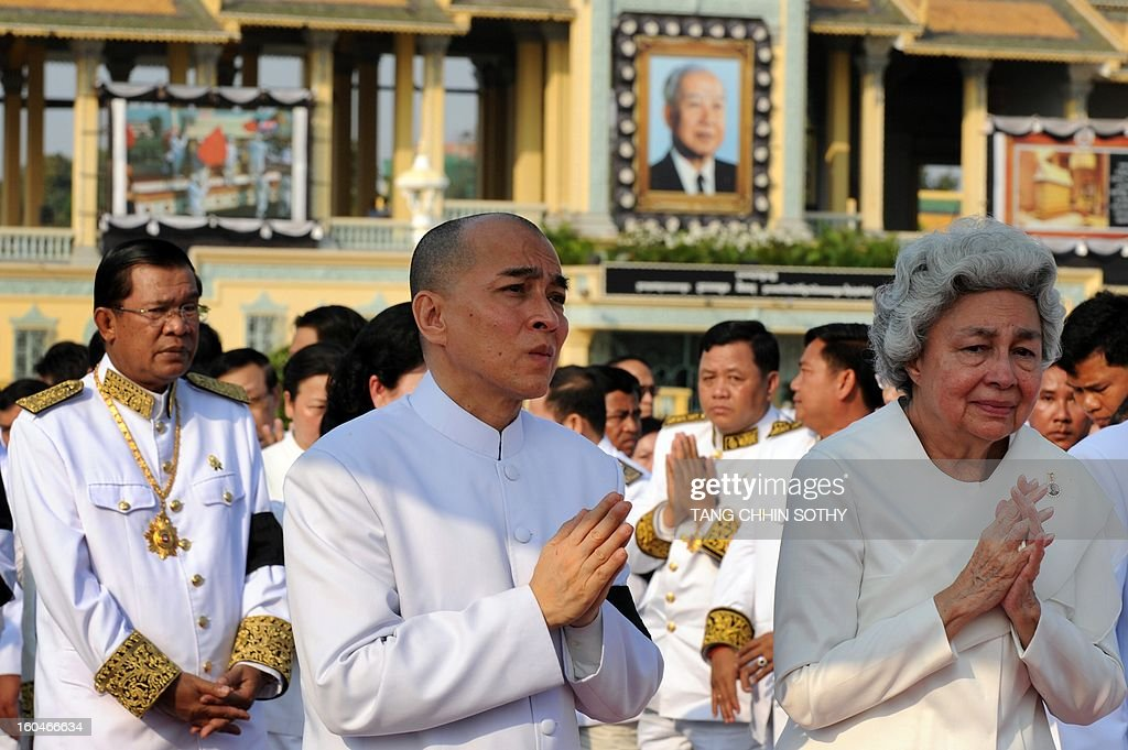 Cambodian Sihanouk's widow Queen Monique (R), King Norodom Sihamoni (C) and Prime Minister Hun Sen (L) sreact during a funeral procession for the late former King Norodom Sihanouk in front of the Royal Palace in Phnom Penh on February 1, 2013. A sea of mourners filled the streets of the Cambodian capital on February 1 for a lavish funeral for revered former king Norodom Sihanouk, who towered over six tumultuous decades in his nation's history. AFP PHOTO/ TANG CHHIN SOTHY
