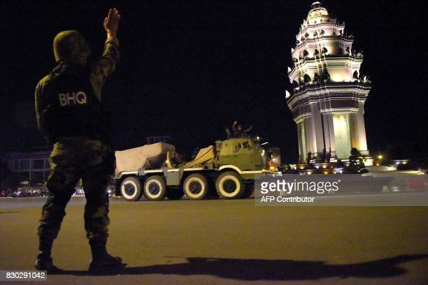A Cambodian soldier waves to others sitting on a rocket launcher truck riding along a street in Phnom Penh in the early hours of August 12 2017...