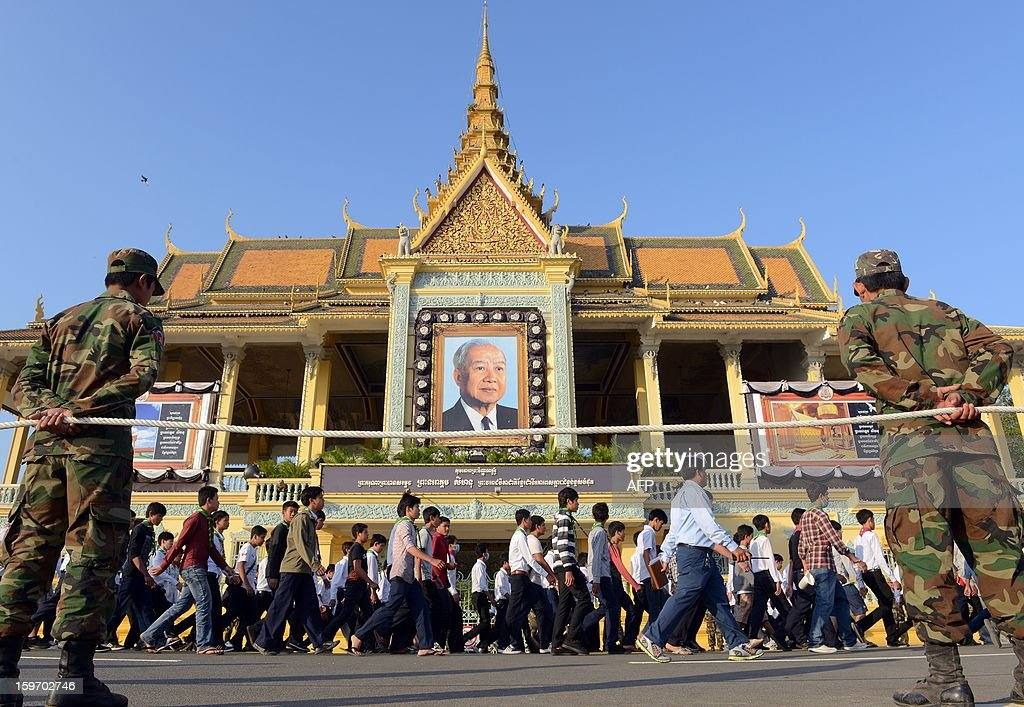 Cambodian soldiers look on as students march during a funeral march procession rehearsal for the late former King Norodom Sihanouk in front of the Royal Palace in Phnom Penh on January 19, 2013. Cambodia's beloved former monarch Norodom Sihanouk, who died aged 89 last month, will be cremated on February 4 following an elaborate ceremony, Cambodian Prime Minister Hun Sen said on November 26, 2012. AFP PHOTO/ TANG CHHIN SOTHY