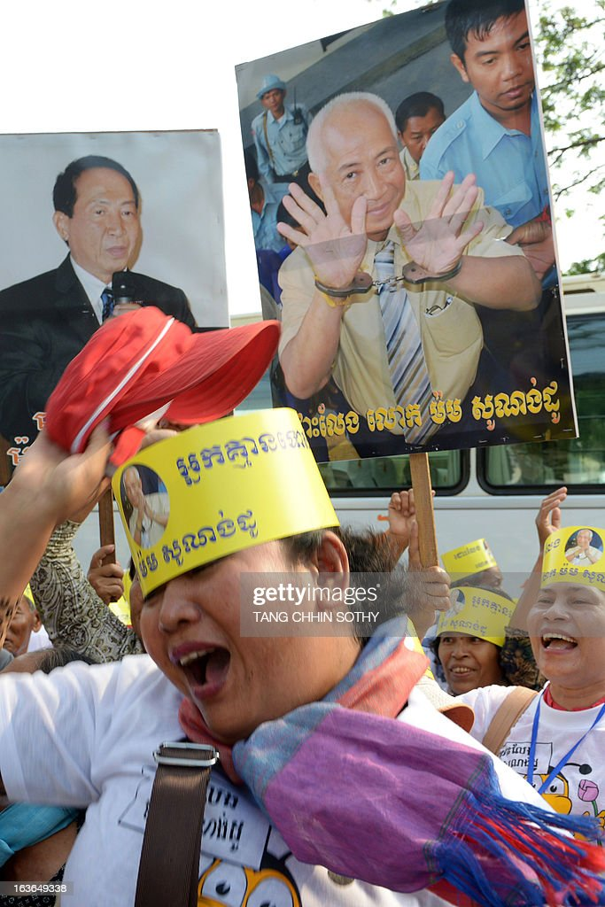 Cambodian supporters of Mam Sonando (pictured on placard back R), owner of the independent Beehive radio station, shout slogans during a protest in front of the Appeal Court in Phnom Penh on March 14, 2013. The Cambodian Appeal Court on March 14 cleared the prominent government critic Sonando, who has dual Cambodian-French citizenship, of a secessionist plot, slashing his 20-year jail term and ordering his release from prison over the next few days.