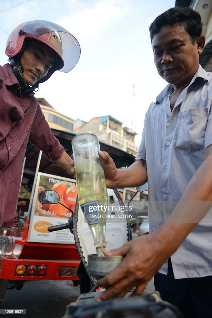 A Cambodian vendor (R) pours gasoline into a motorcycle tank along a street in Phnom Penh on January 4, 2013. Cambodia on December 28, 2012 gave the green light to construction of its first oil refinery, a multi-billion-dollar Chinese-backed project, as the kingdom looks to tap its untouched offshore reserves.