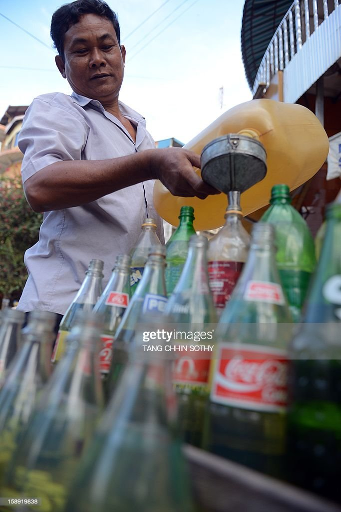 A Cambodian vendor pours gasoline into soft drink glass bottles used for display at his fuel outlet along a street in Phnom Penh on January 4, 2013. Cambodia on December 28, 2012 gave the green light to construction of its first oil refinery, a multi-billion-dollar Chinese-backed project, as the kingdom looks to tap its untouched offshore reserves.