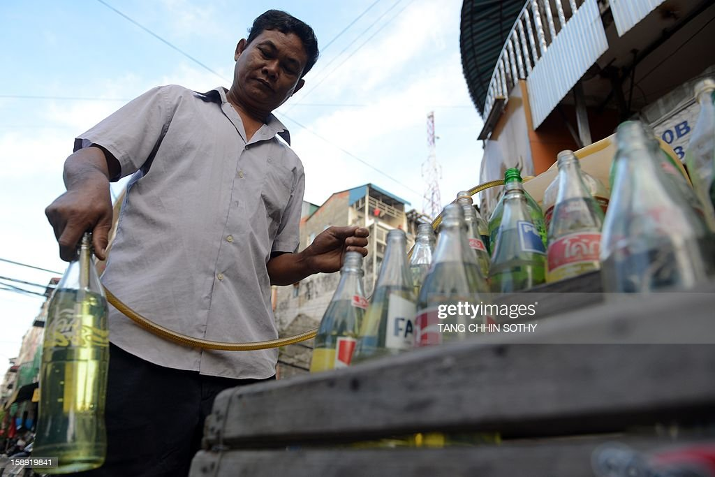 A Cambodian vendor pours gasoline into soft drink glass bottles used for display at his fuel outlet along a street in Phnom Penh on January 4, 2013. Cambodia on December 28, 2012 gave the green light to construction of its first oil refinery, a multi-billion-dollar Chinese-backed project, as the kingdom looks to tap its untouched offshore reserves. AFP PHOTO/ TANG CHHIN SOTHY