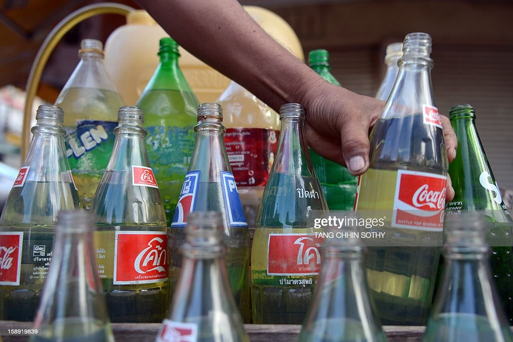 A Cambodian vendor prepares gasoline, stored in soft drink glass bottles, for sale along a street in Phnom Penh on January 4, 2013. Cambodia on December 28, 2012 gave the green light to construction of its first oil refinery, a multi-billion-dollar Chinese-backed project, as the kingdom looks to tap its untouched offshore reserves. AFP PHOTO/ TANG CHHIN SOTHY