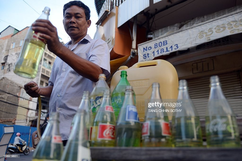A Cambodian vendor prepares gasoline, stored in soft drink glass bottles, for sale along a street in Phnom Penh on January 4, 2013. Cambodia on December 28, 2012 gave the green light to construction of its first oil refinery, a multi-billion-dollar Chinese-backed project, as the kingdom looks to tap its untouched offshore reserves.