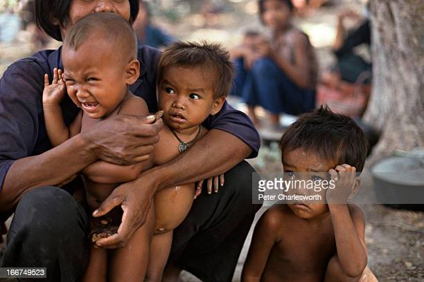 Cambodian woman and her children who have been repatriated from a refugee camp in Thailand by UNTAC sit in a small village that is surrounded by land...