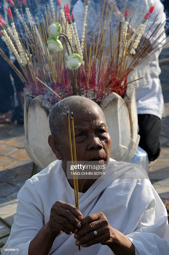 A Cambodian woman burns incense to pay her respects to the late former king Norodom Sihanouk in front of the Royal Palace in Phnom Penh on February 3, 2013. Thousands of Cambodians have paid their last respects to their beloved former king Norodom Sihanouk as his body lay in state ahead of his cremation on February 4.