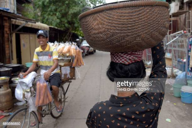 A Cambodian woman carries a basket of food as a man rides a bicycle loaded with breads for sale past the residential complex known as White Building...
