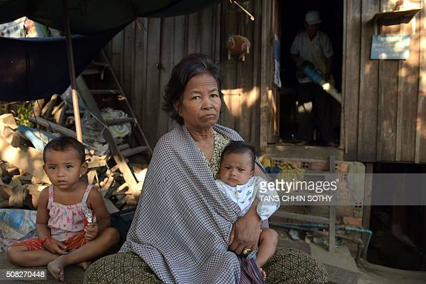 A Cambodian woman holds a baby as a health official uses an aspirator to collect mosquitoes in effects to stem any outbreak of the Zika virus in...