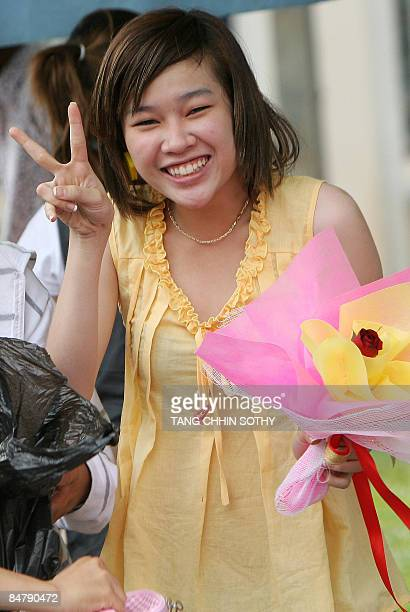 A Cambodian woman holds a Valentine's day flower along a street in Phnom Penh on February 14 2009 Valentine's Day or Saint Valentine's Day is...